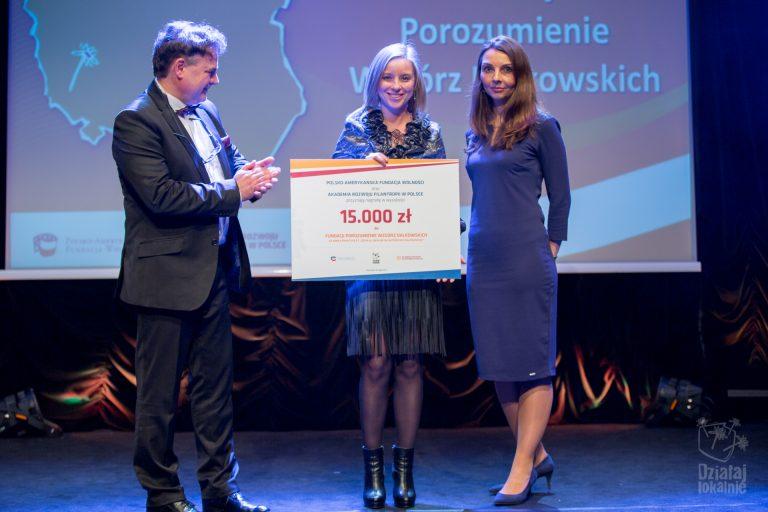 Przedstawicielka Fundacji Porozumienie Wzgórz Dalkowskich odbiera symboliczny czek z nagrodą w konkursie na dobre praktyki