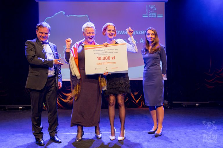 Przedstawicielki Stowarzyszenia Kraina św. Anny odbierają symboliczny czek z nagrodą w konkursie na dobre praktyki