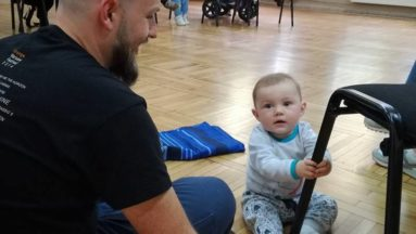 Tatuś siedzący na ziemi razem z synem