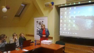 Zdjęcie przedstawia osoby słuchające szkoleniowca kobietę. W tle ekran projektora.