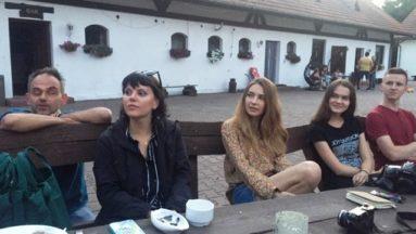 Zdjęcie przedstawia pięć osób siedzących przy stole i słuchających osoby przemawiającej