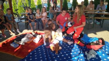 Zdjęcie przedstawia ratowników medycznych, którzy tłumaczą dzieciom zasady udzielania pierwszej pomocy.