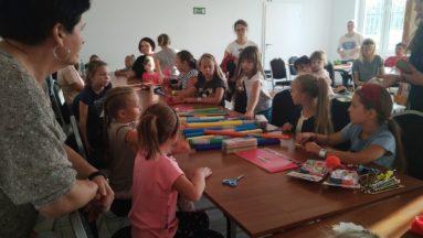 zdjęcie przedstawia grupę dzieci siedzących przy stole, na którym znajdują się materiały plastyczne