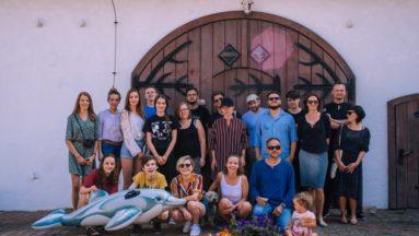 Zdjęcie przedstawia grupę młodych ludzi wraz z nauczycielami, na tle dużych, drewnianych drzwi.