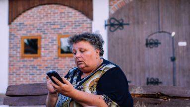 Zdjęcie przedstawia kobietę, korzystającą z telefonu komórkowego