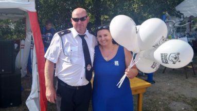 """Zdjęcie przedstawia kobietę i mężczyznę. Kobieta trzyma w ręku kila baloników z logiem """"Działaj Lokalnie"""", mężczyzna ubrany jest w mundur Ochotniczej Straży Pożarnej"""