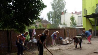 Wolontariusze grabią trawę w ogrodzie