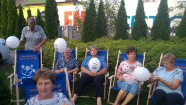 Uczestnicy spotkania: Kino w plenerze na niebieskich leżakach z logo Działaj Lokalnie.