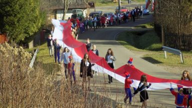 Młodzież i dzieci z Ropienki maszerują ze 100-tu metrową flagą państwową