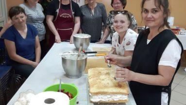 Zdjęcie przedstawia osoby biorące udział w warsztatach kulinarnych w trakcie dekoracji tortu.