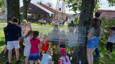 Zdjęcie przedstawia grupę dzieci i dorosłych podczas obchodów Dnia Dziecka.