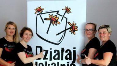 Zdjęcie przedstawia cztery kobiety ubrane w koszulki z logiem KGW Czilibabki, stojące przy banerze z logiem Działaj Lokalnie.