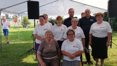 Zdjęcie przedstawia kobiety ubrane w koszulki KGW Kaszów oraz innych uczestników wydarzenia, pozujących do zdjęcia w plenerze.