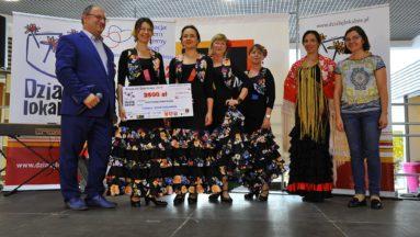 Zdjęcie przedstawia grupę osób pozujących do zdjęcia. Cztery kobiety ubrane w suknie do flamenco trzymają symboliczny czek na grant programu Działaj Lokalnie.