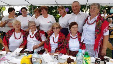 Zdjęcie przedstawia członkinie Koła Gospodyń Wiejskich wraz z innymi uczestnikami wydarzenia, pozujących do zdjęcia przy zastawionym stole.