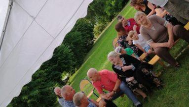 Zdjęcie przedstawia osoby siedzące na widowni pod piknikowym namiotem.