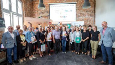 Zdjęcie przedstawia grupę osób pozujących do zdjęcia, trzymających dyplomy dla grantobiorców.