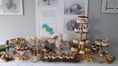 Zdjęcie przedstawia stół z poukładanymi na nim ciasteczkami i innymi słodkościami.