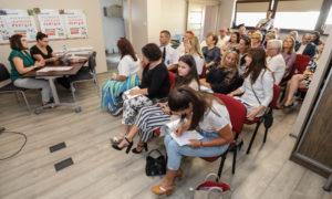 Zdjęcie przedstawia grupę osób we wnętrzu, siedzących naustawionych wrzędach czerwonych krzesłach. Nadrugim planie, dwie kobiety siedzą przystoliku zwróconym wstronę grupy siedzących osób.