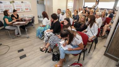 Zdjęcie przedstawia grupę osób we wnętrzu, siedzących na ustawionych w rzędach czerwonych krzesłach. Na drugim planie, dwie kobiety siedzą przy stoliku zwróconym w stronę grupy siedzących osób.