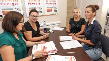 Zdjęcie przedstawia cztery osoby siedzące przy stole, na którym znajdują się promesy na granty programu Działaj Lokalnie.
