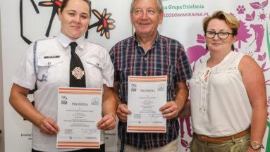 Zdjęcie przedstawia trzy osoby z uśmiechem pozujące do zdjęcia. Dwie z nich trzymają podpisane promesy na granty.