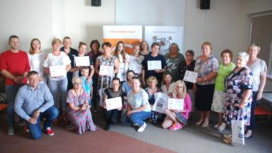 Zdjęcie przedstawia grupę osób we wnętrzu. Osoby pozują do zdjęcia; niektóre z nich trzymają symboliczne czeki na granty programu Działaj Lokalnie.