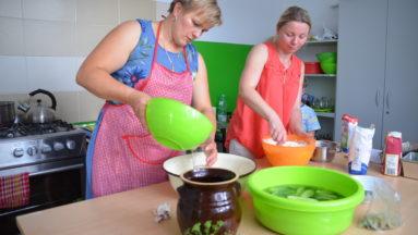 Zdjęcie przedstawia dwie kobiety w kuchni, stojące przy stole i przygotowujące dania.