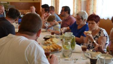Zdjęcie przedstawia biesiadujące osoby, siedzące przy stole.