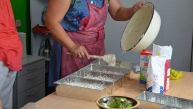 Zdjęcie przedstawia kobietę nakładającą ciasto chlebowe do foremek stojących na stole w kuchni.