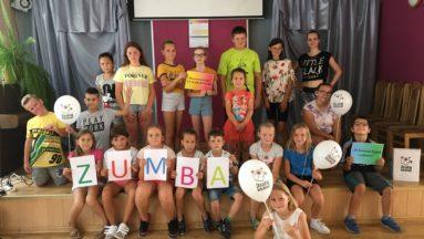 """Zdjęcie przedstawia grupę dzieci na sali gimnastycznej, pozujących do zdjęcia. Dzieci w pierwszym rzędzie trzymają kartki tworzące napis ZUMBA, a kilkoro innych dzieci trzyma balony z logiem """"Działaj Lokalnie""""."""