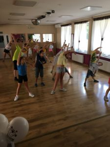 Zdjęcie przedstawia dzieci nasali gimnastycznej wykonujące ćwiczenie podczas zajęć zzumby.