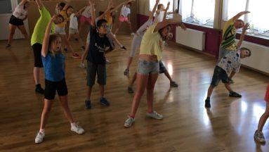 Zdjęcie przedstawia dzieci na sali gimnastycznej wykonujące ćwiczenie podczas zajęć z zumby.