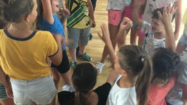 Zdjęcie przedstawia dzieci stojące w kółku, podnoszące ręce do góry.