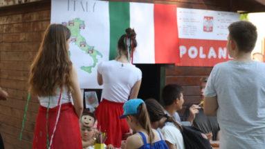 Zdjęcie przedstawia kilkoro młodych ludzi, oglądających plakaty na temat Włoch i Polski.
