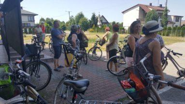 Zdjęcie przedstawia uczestników rajdu, stojących wśród swoich rowerów.