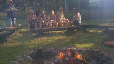 Zdjęcie przedstawia grupę uczestników rajdu, siedzących przy ognisku.