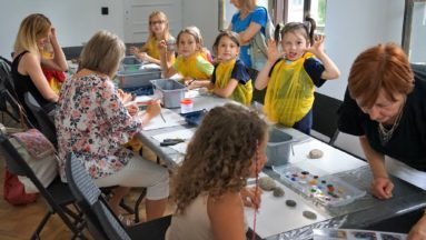 Zdjęcie przedstawia grupę dorosłych i dzieci siedzących przy stole, na którym rozłożone są przybory do malowania, kartki oraz kamienie.