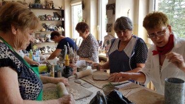 Zdjęcie przedstawia seniorki siedzące przy stole tworzące ceramiczne medale.