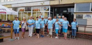 Zdjęcie przedstawia grupę seniorów, ubranych wkoszulki znazwą projektu, pozujących dozdjęcia.