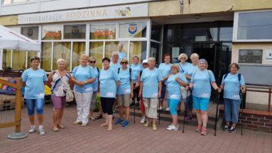 Zdjęcie przedstawia grupę seniorów, ubranych w koszulki z nazwą projektu, pozujących do zdjęcia.