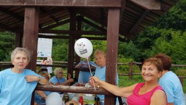 """Zdjęcie przedstawia grupę seniorów w plenerze; jedna pani trzyma balon z logiem """"Działaj Lokalnie""""."""