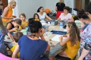 Na zdjęciu widać duży stół, naktórym rozłożone są farby, kartki papieru orazkamienie. Dookoła stołu siedzą dzieci orazdorośli, przygotowujący się dowarsztatów plastycznych.
