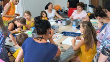 Na zdjęciu widać duży stół, na którym rozłożone są farby, kartki papieru oraz kamienie. Dookoła stołu siedzą dzieci oraz dorośli, przygotowujący się do warsztatów plastycznych.