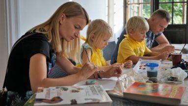 Zdjęcie przedstawia dwójkę dzieci oraz dwójkę dorosłych, siedzących przy stole, na którym znajdują się przybory artystyczne. Wszystkie osoby widoczne na zdjęciu skupione są na malowaniu kamieni.
