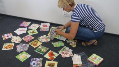 Zdjęcie przedstawia instruktorkę zajęć kucającą wśród rozłożonych na podłodze kartek z dziełami powstałymi podczas warsztatów decoupage.