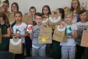 Zdjęcie przedstawia grupę dzieci pozujących dozdjęcia zwłasnoręcznie wykonanymi papierowymi torbami.
