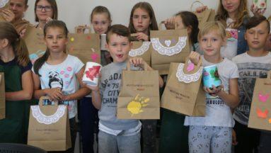 Zdjęcie przedstawia grupę dzieci pozujących do zdjęcia z własnoręcznie wykonanymi papierowymi torbami.