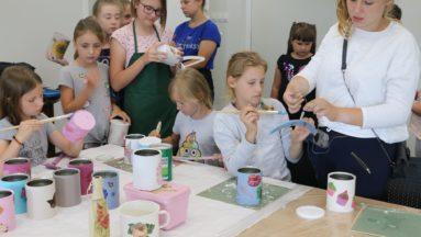 Zdjęcie przedstawia grupę dzieci i dorosłych podczas warsztatów decoupage.