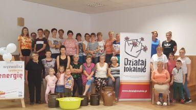 Zdjęcie przedstawia grupę osób pozujących do zdjęcia we wnętrzu, dookoła baneru z logiem programu Działaj Lokalnie.